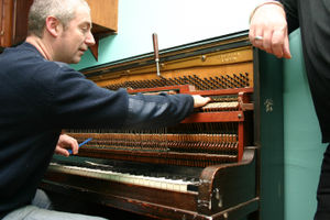 Piano maintenance - A piano tuner at work