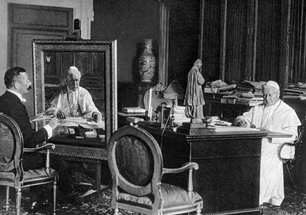 Pius X in his study while receiving a portraiture. Nearby is a statue of John Vianney. PiusXstudy.jpg