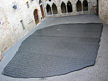 Photo depicting a large copy of the Rosetta Stone filling an interior courtyard of a building in Figeac, France