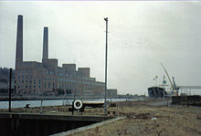 Large building with two chimneys seen across a dock with one boat moored.