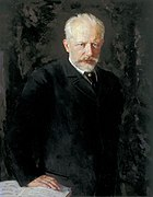 A middle-aged man with grey hair and a beard, wearing a dark suit and staring intently at the viewer