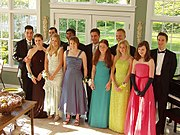 A typical pre-prom gathering, with girls in dresses, and boys in tuxedos.