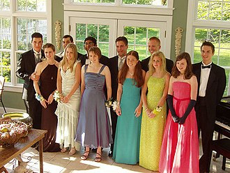 Prom - A typical gathering, with boys in tuxedos, and girls in dresses with corsages on their wrists.