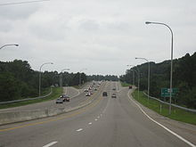 Uphill view of a four-lane divided freeway approaching an exit off-ramp