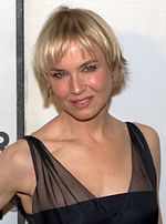 Profile of a female with short blonde hair wearing a black dress.
