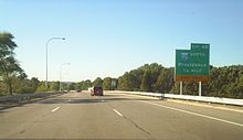 Ground-level view of three lanes of a divided freeway; a large, green exit signs is visible to the right, and trees surround the freeway on both sides.