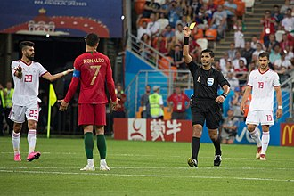 Video assistant referee - Cristiano Ronaldo (Portugal) being shown a yellow card after a challenge with Iranian player that was reviewed by referee Enrique Cáceres as a potential red card incident