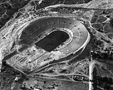 A black-and-white aerial image of a dirt field with horseshoe shaped seating around it
