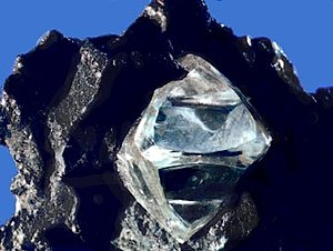 Diamond - The slightly misshapen octahedral shape of this rough diamond crystal in matrix is typical of the mineral. Its lustrous faces also indicate that this crystal is from a primary deposit.