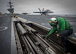 Sailor performs maintenance on a catapult on the flight deck of USS Carl Vinson. (26951190803).jpg