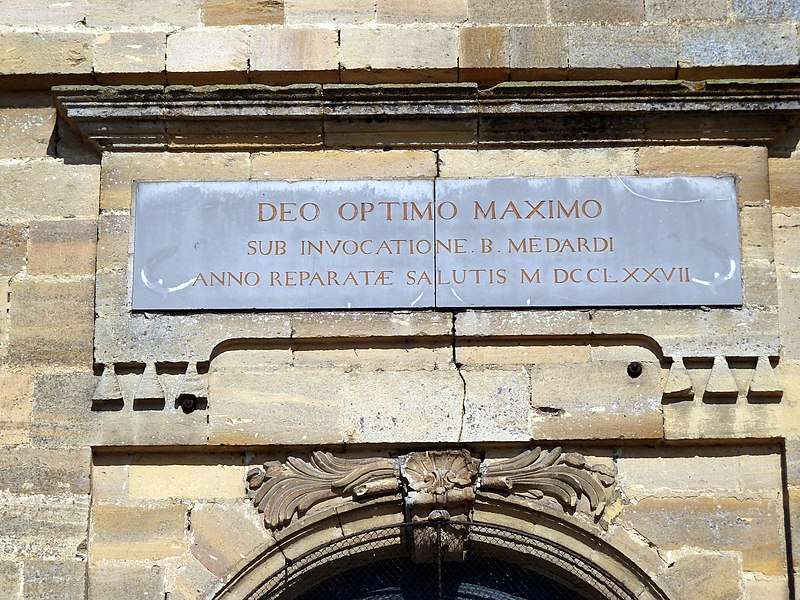 Saint-Mard-sur-le-Mont eglise - Inscription au dessus de la porte principale où figure la date de construction en chiffres romains: MDCCLXXVII = 1777. On trouve également une information sur le fait que l'église est dédiée à saint Médard.