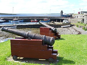 Shapinsay - Cannon decorate the quayside of Balfour Harbour on Shapinsay, the round tower in the background is The Douche