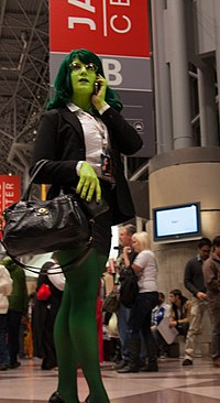 Cosplay de Miss Hulk en costume d'avocate.