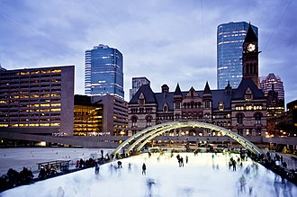 Nathan Phillips Square is the city's main square. The square includes a reflecting pool that is converted into an ice rink during the winter. Skaters at dusk.jpg