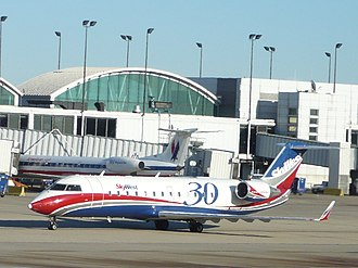 "Aircraft livery - SkyWest Airlines celebrated its 30th anniversary in 2007. Notice the red and blue nontraditional ""wavy"" cheatline along the fuselage compared to the more traditional linear cheatline of American Eagle regional jet in the background."
