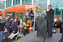 Mayor Greg Nickles speaking from a podium to a crowd of people, including several camera operators, with an orange streetcar in the background.