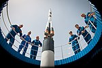 Soyuz MS-09 crew and backup crew at the Soyuz rocket monument behind the Cosmonaut Hotel.jpg