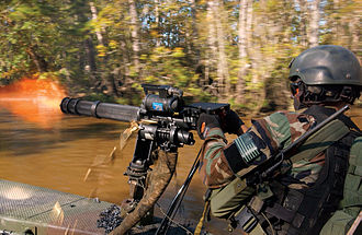 "Suppressive fire - U.S. Special Warfare combatant-craft crewmen use a rotating barrel minigun to lay down suppressing fire during a practice ""hot"" extraction of forces on a beach."