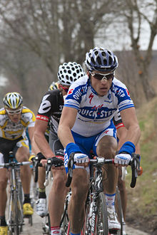 A road racing cyclist wearing a white and blue jersey with red trim and sunglasses leads a line of other cyclists. Partially visible behind him are a cyclist in a black and white jersey and one in a white and yellow jersey.