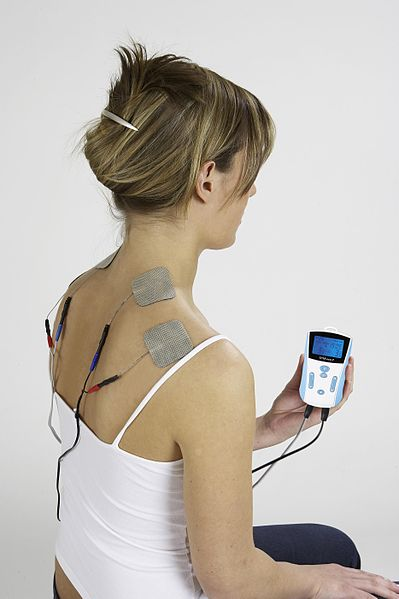 Woman using portable TENS Unit