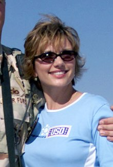 "A candid photo of a Caucasoid woman in sunglasses and a ""USO"" shirt; an arm is wrapped around her back, holding her left shoulder, and she is looking to the camera's right."