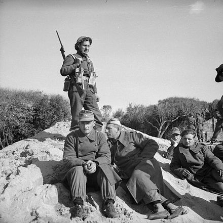 A British soldier guards a group of German prisoners at Anzio, 22 January 1944. The British Army in Italy 1944 NA11058.jpg