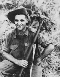 An informal portrait of a man in military uniform holding a rifle.