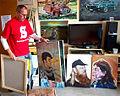 Tommy tallstig med några av sina porträttmålningar.jpg