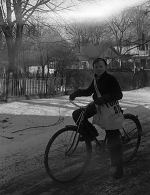 A boy on a bicycle with a Toronto Star newspap...