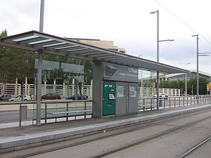 Trambesòs - View of one of the railway platforms, the tracks and one of the shelters of Auditori – Teatre Nacional tram stop. Several facilities such as the ticket machine, two noticeboards and a passenger information display (PID) screen can be seen.