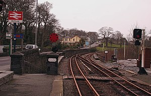 Minffordd railway station - Transport Interchange at Minffordd - bus stop on far left of picture; left of picture ramp/subway to National Rail platform; and centre/right Ffestiniog Railway tracks, ends of platforms and foot crossing, and in the middle, the slope down to the Cambrian Coast Line platform.