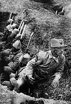 Soldiers in a trench, with one looking in a different direction