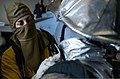 U.S. Navy Aviation Boatswain's Mate (Handling) Daniel Bymer-Schultz, left, assists a shipmate with donning protective gear during a firefighting drill in the hangar bay of the aircraft carrier USS Nimitz 130410-N-TW634-028.jpg