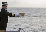 U.S. Navy Capt. David L. Bossert, the executive officer of the amphibious assault ship USS Kearsarge (LHD 3), releases the ashes of a Sailor during a burial at sea March 19, 2013, aboard the ship in the Atlantic 130319-M-BS001-005.jpg