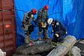 U.S. Soldiers with the Massachusetts Army National Guard and a member of the Federal Emergency Management Agency Urban Search and Rescue Task Force 1 clear rubble at the site of a simulated collapsed building 131106-Z-UR570-006.jpg