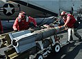 US Navy 041004-N-4565G-003 Aviation Ordnancemen move a skid loaded with three GBU-16 1,000 lb. laser guided bombs across the flight deck aboard the conventionally powered aircraft carrier USS John F. Kennedy (CV 67).jpg
