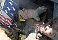 US Navy 041113-M-1250B-007 A U.S. Navy Seabee assigned to the 24th Marine Expeditionary Unit (MEU), wields two pieces of metal together with a blow-torch as he helps repair a bridge in Lutafiyah, Iraq.jpg