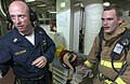 US Navy 060526-N-9851B-007 Engineering Training Team (ETT) leader, Master Chief Engineman Kevin Colligan, discusses the performance of fire teams involved with fighting a simulated fire in the number two auxiliary machine room.jpg