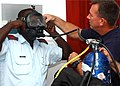 US Navy 061110-N-4205W-003 Senior Chief Navy Master Diver Gene McDaniel, assigned to Mobile Diving and Salvage Unit One (MDSU-1) Detachment 5, based in Pearl Harbor, Hawaii, explains the Mk 20 full face mask to Seychelles Coast.jpg