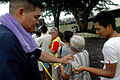 US Navy 070706-N-9421C-059 Aviation Boatswain's Mate (Handling) 3rd Class Eduardo Ople shares a snack with a resident while waiting in line to be seen by the Pacific Partnership medical staff at Gogon Elementary School.jpg