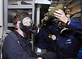 US Navy 081203-N-2013O-017 Ship's Serviceman 3rd Class Amanda Rampulla, from Wapakoneta, Ohio, helps Culinary Specialist 2nd Class Vaughn Green, from Mesa, Ariz., drink water through a MCU-2P gas mask.jpg