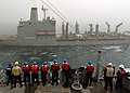 US Navy 090212-N-9134V-001 Sailors aboard the amphibious dock landing ship USS Carter Hall (LSD 50) watch as the Military Sealift Command fleet replenishment oiler USNS Tippecanoe (T-AO 199) comes alongside the ship for a reple.jpg