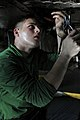 US Navy 091224-N-7939W-050 Aviation Machinist's Mate Seaman Christopher King, assigned to the Warhawks of Strike Fighter Squadron (VFA) 97, conducts maintenance on wiring on an F-A-18C Hornet aboard the aircraft carrier USS Nim.jpg