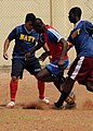 US Navy 100412-N-6676S-083 Information Systems Technician 2nd Class Mark Cervantes nd Boatswain's Mate Seaman Jean Petitfrere try to strip the ball from a Senegalese navy soccer team player during a soccer match.jpg