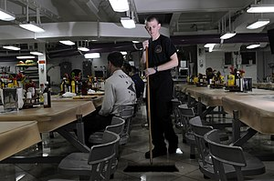 US Navy 120124-N-RG587-172 Aviation Electrician's Mate Airman Grant Godfrey sweeps the mess decks aboard the Nimitz-class aircraft carrier USS Carl.jpg
