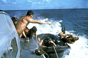 United States Navy SEALs - UDT members using the casting technique from a speeding boat.