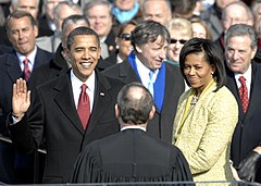 Barack Obama holds his right hand in the air as he and Michelle Obama both smile towards a balding man whose back is to the camera while a large crowd watches.