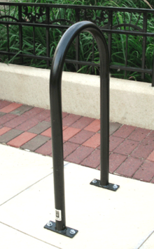 A tube of black-painted metal bent into a tall U shape and bolted at both ends to a concrete slab, in front of a brick pathway and iron railings