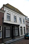 foto van Huis met gepleisterde gevel, waarin sierankers, onder kroonlijst