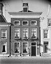 foto van Pand onder zadeldak met gevel met bloklijst aan de kroonlijst en oude schoorsteen boven voorste dakschild
